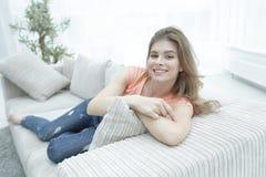 在家放松在长沙发的年轻女学生 免版税库存图片