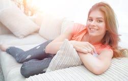 在家放松在长沙发的年轻女学生 免版税库存照片