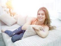 在家放松在长沙发的年轻女学生 库存照片