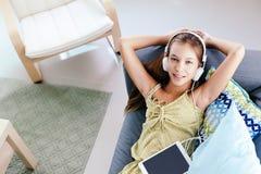 在家放松在长沙发的非离子活性剂女孩 免版税库存照片
