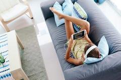 在家放松在长沙发的非离子活性剂女孩 库存照片