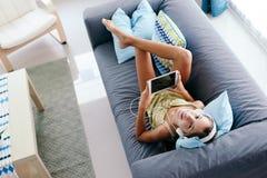 在家放松在长沙发的非离子活性剂女孩 图库摄影