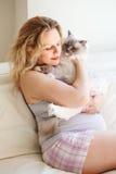 在家放松在长沙发的年轻白白种人白肤金发的孕妇在T恤杉和短裤画象有长的头发的拿着猫 免版税库存图片