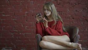 在家放松微笑的女孩,她连接和社会网络用她的智能手机 股票视频