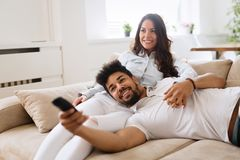 在家放松愉快的夫妇一起说谎在沙发和 库存照片