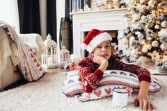 在家放松由圣诞树的孩子 免版税库存图片