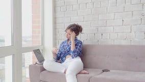 在家放松谈话在电话和研究膝上型计算机的愉快的妇女 影视素材