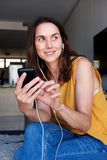 在家放松通过听的可爱的老妇人到与巧妙的电话和耳机的音乐 免版税库存照片