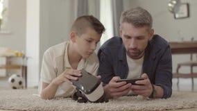 在家放置在蓬松地毯的地板的爸爸和儿子使用虚拟现实玻璃,愉快的友好的家庭 股票视频
