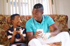 在家教移动电话技术的父亲对男孩 图库摄影