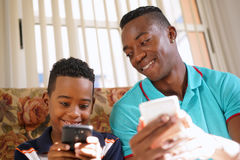 在家教移动电话技术的黑人对男孩 库存照片