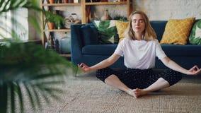 在家是松弛在Badha Konasana位置实践的蝴蝶瑜伽姿势享受休息的灵活的小姐和 影视素材