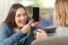 在家显示一个空白的电话屏幕的女孩对朋友 免版税库存图片