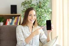 在家显示电话屏幕的妇女 库存照片