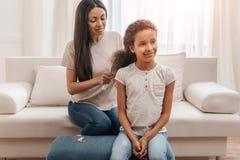 在家梳头发的美国黑人的母亲对小女儿 库存图片
