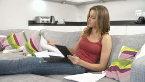 在家检查财务的少妇使用数字式片剂 影视素材