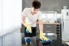在家清洗现代厨房的亚裔年轻人 免版税库存图片