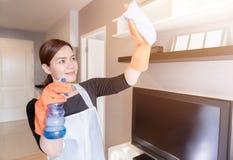 在家清洗镜子的年轻佣人与浪花,清洗服务概念 免版税库存照片