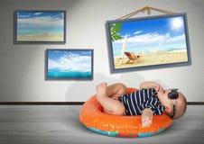 在家游泳圈子的滑稽的婴孩,在海滩 假期 库存图片