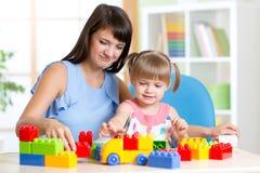 在家演奏与母亲的逗人喜爱的小女孩块 免版税库存图片