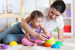 在家演奏块玩具的妈妈和孩子 免版税库存图片
