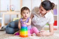 在家演奏块玩具的妈妈和孩子 免版税图库摄影