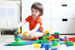 3年在家演奏塑料块的儿童 免版税库存照片