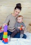 在家演奏塑料块的妈妈和婴孩 免版税库存图片