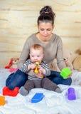 在家演奏塑料块的妈妈和婴孩 图库摄影