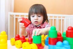 在家演奏塑料块的小孩画象 免版税库存照片