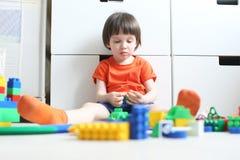 在家演奏塑料块的小男孩(3年) 免版税库存照片