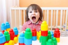 在家演奏塑料块的愉快的小男孩 免版税图库摄影