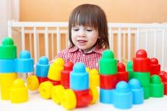 在家演奏塑料块的愉快的小男孩 免版税库存照片