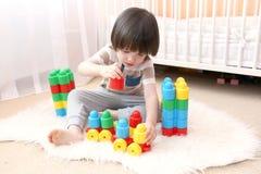 在家演奏塑料块的逗人喜爱的小男孩 免版税库存照片