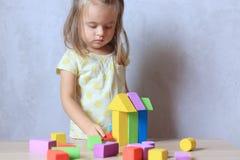 在家演奏建设者玩具的儿童女孩 免版税图库摄影