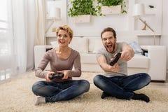 在家演奏控制台的激动的已婚夫妇 库存照片