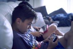 在家演奏控制台的男孩 库存图片