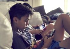 在家演奏控制台的男孩 图库摄影