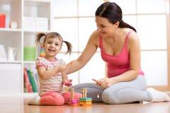 在家演奏教育玩具的逗人喜爱的妇女和孩子女孩 库存照片