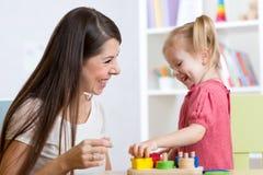 在家演奏教育玩具的逗人喜爱的妇女和孩子女孩 免版税库存图片