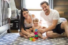 在家演奏有母亲和父亲的儿童小孩玩具或幼儿园 免版税图库摄影