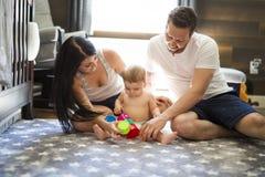 在家演奏有母亲和父亲的儿童小孩玩具或幼儿园 免版税库存图片