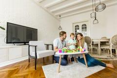 在家演奏有母亲和父亲的小男孩玩具 库存图片