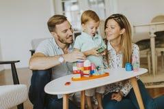 在家演奏有母亲和父亲的小男孩玩具 库存照片
