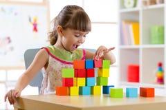 在家演奏木玩具或幼儿园的儿童小女孩 库存照片