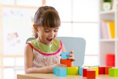 在家演奏木玩具或幼儿园的儿童小女孩 库存图片