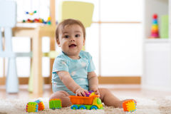 在家演奏木玩具或幼儿园的婴孩 免版税库存照片