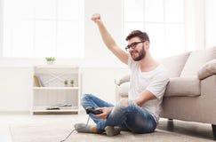 在家演奏电子游戏和胜利的愉快的人 免版税库存图片