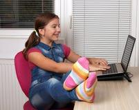 在家演奏膝上型计算机的小女孩 图库摄影