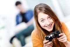 在家演奏计算机游戏的美丽的妇女画象 免版税图库摄影